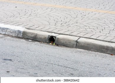Sidewalk with yellow mark and street with gutter pipe
