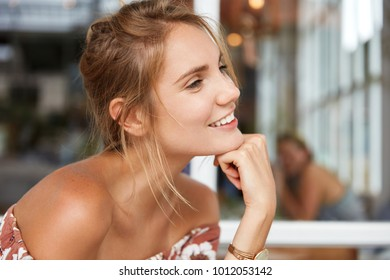 Sideways close up portrait of cheerful beautiful female model with naked shoulders, leans at hand, looks thoughfully and happily aside, remembers or dreams about something pleasant, rests alone