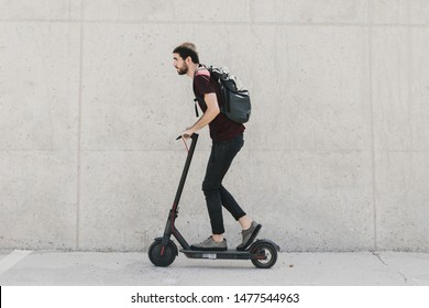 Sideways man riding an e-scooter
