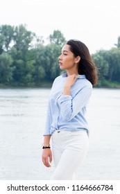 Sideways portrait of a beautiful brunette woman in nature. Walk, business, summer concept