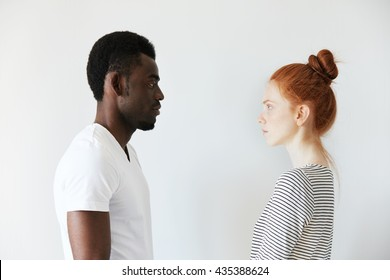 Sideways portrait of a couple looking each other in the eyes on white background. Afro man standing still and Caucasian redhead girl as well watching him with serious look like wife on husband.