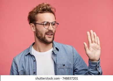 Sideways portrait of fashionable young male notices someone, greets reluctantly, waves with palm unwillingly, being not glad to meet old boring friend. Displeased man says hello to fore girlfriend