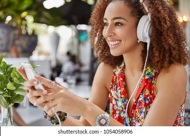 Sideways portrait of happy African American female student with dark skin learns foreign language on audiobook downloaded on smart phone, listens audio in modern white headphones with happy look