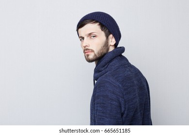 Sideways portrait of natural brunette Caucasian man wearing warm clothes on white background. Bearded hipster with stylish well-trimmed mustache looking serious and brutal at the camera.