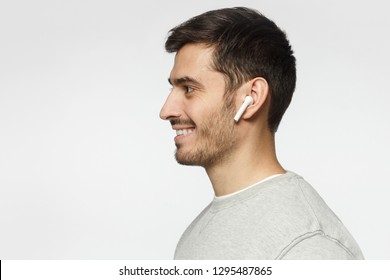 Sideways portrait of smiling young man listening to music or radio, uses modern wireless earphones