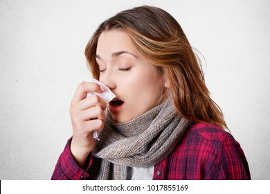 Sideways portrait of young woman has allergic rhinitis, sneezes into napkin, has headache, wears scarf on neck, isolated over white background. Sickness, seasoanl virus and health problem concept