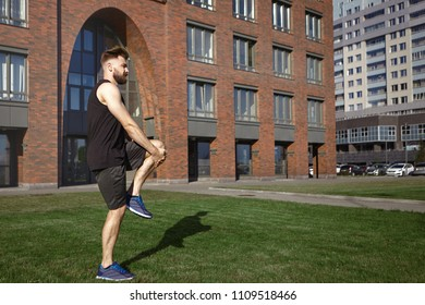 Sideways shot of attractive young European bearded male runner wearing stylish black sports outfit and running shoes standing on grass, embracing his left knee, stretching quadricep muscles