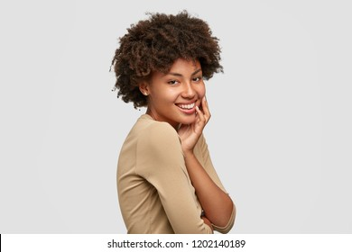 Sideways shot of cheerful dark skinned young model with Afro haircut, has gentle smile, dressed in casual beige sweater, models in studio against white background. People and ethnicity concept