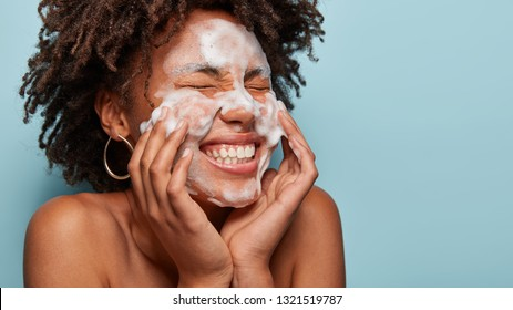 Sideways shot of pleasant looking lady applies cosmetic foam, feels pleasure after beauty treatments, polishes face, isolated over blue background with empty space on left side for your text