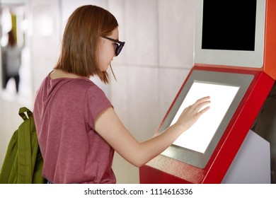 Sideways shot of pretty female carries rucksack, wears shades, stands in front of terminal, tries to transfer money on her cellular account, touches screen, makes transactions. People and finances