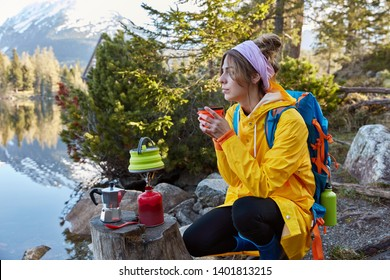 Sideways shot of thoughtful traveller enjoys hot drink from disposable cup near mountain lake, being deep in thoughts, makes hot drink on camp stove, wears casual clothes, has rucksack on back