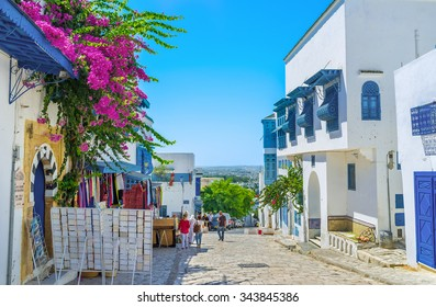 SIDI BOU SAID, TUNISIA - AUGUST 31, 2015: The picturesque shopping street with white restored villas and small souvenir stalls, on August 31 in Sidi Bou Said.