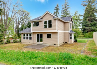 Siding house with tile roof. Backyard concrete porch overlooking green nature