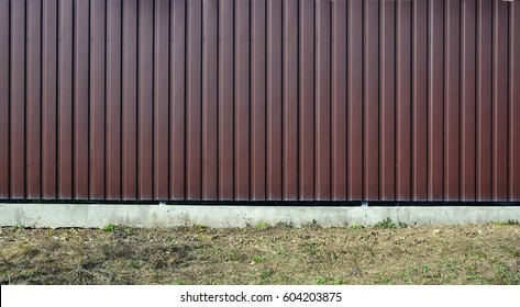 Siding, metal panels texture closeup in the daytime outdoors. Metal wall or fence embossed metal sheets. Terrain and large metal sheet as a barrier or fence