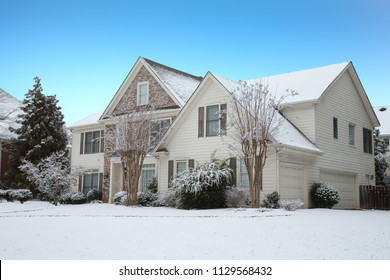 Siding and Stone House in Snow under Blue