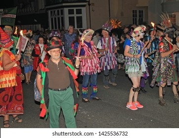 SIDMOUTH, DEVON, ENGLAND - AUGUST 10TH 2012: A group of Morris dancers dressed in flowered hats and ragged waistcoats take part in the night time closing procession of folk week