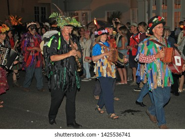 SIDMOUTH, DEVON, ENGLAND - AUGUST 10TH 2012: A group of musicians dressed in flowered hats and ragged waistcoats take part in the night time closing procession of folk week