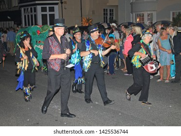SIDMOUTH, DEVON, ENGLAND - AUGUST 10TH 2012: A group of musicians dressed in decorated top hats and ragged blue waistcoats take part in the night time closing procession of folk week