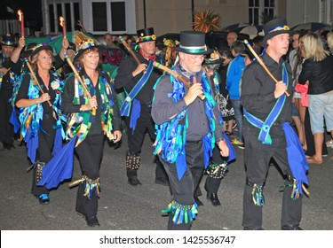 SIDMOUTH, DEVON, ENGLAND - AUGUST 10TH 2012: A group of Morris dancers dressed in decorated top hats and ragged blue waistcoats take part in the night time closing procession of folk week