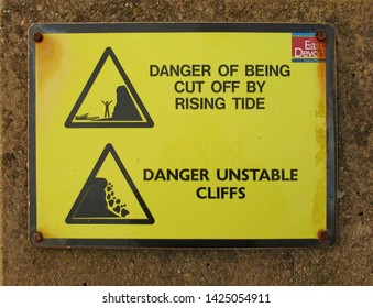SIDMOUTH, DEVON,ENGLAND - JANUARY 23RD 2019: Sign at Sidmouth sea front telling of the dangers of rising tides and falling cliffs.