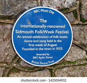 SIDMOUTH, DEVON,ENGLAND - JANUARY 23RD 2019: A blue commemorative plaque about the annual folk week held in Sidmouth during the first week in August each year.