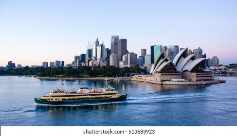 SIDNEY, AUSTRALIA - NOVEMBER 2, 2016: A passenger ferry passes in front of the Sidney Opera House in the early morning, with the skyline of the city in the background.