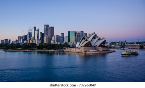 SIDNEY, AUSTRALIA - NOVEMBER 2, 2016: Passenger ferry passes in front of the Sidney Opera House, with the city skyline in the background against the early morning sky.
