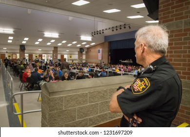 SIDNEY, OH - OCTOBER 6, 2014. A security guard looks out over students in the cafeteria at lunch time.