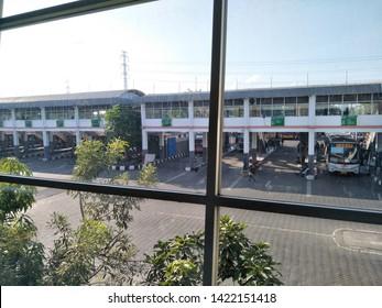 Sidoarjo, Indonesia - May 30th 2019: Bus parked in Terminal Bungurasih with the atmosphere of people return to their hometown by Bus. or it called Suasana Mudik, or Pulang Kampung dengan Bis drive run