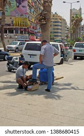 SIDON (SAIDA), LEBANON - MAY 30 2004: Seated shoeshine boy shines shoe of man standing in front of him on sunny pavement/sidewalk, under shade of palm tree, with buildings and traffic in background.