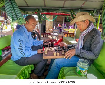 Siem Reap, Cambodia - 12/03/2016: Two tuk tuk drivers take a break playing a game of chess in Siem Reap, Kingdom of Cambodia. Chess is played throughout most of Southeast Asia.