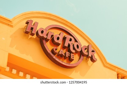 """Siem Reap, Cambodia - 20 March 2018: Logo of famous brand """"Hard Rock cafe"""" in Siem Reap, Cambodia. Hard rock cafe brand label on sky background. Yellow musical cafe building. Famous night out place"""