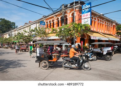 SIEM REAP, CAMBODIA - 23 DEC 2013: Tuk-tuk tourist taxi on the central street of the town with colonial architecture buildings