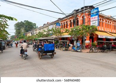 SIEM REAP, CAMBODIA - 23 DEC 2013: Typical traffic passes a colorful building in Siem Reap, Cambodia.