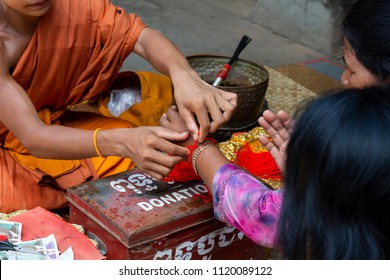 Siem Reap, Cambodia - 25 March 2018: Buddhist monk giving string bracelet in Angkor Wat temple. Buddhist ritual of chanting mantra and bless. Buddhist bracelet from red thread. Angkor Wat scene