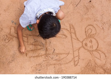 SIEM REAP, CAMBODIA - APR 07: An unidentified boy drawing animation on the sand in Angkor Wat temple, Angkor archaeological park, Cambodia. He draw the man-monkey of Hindu. On April 07, 2014.