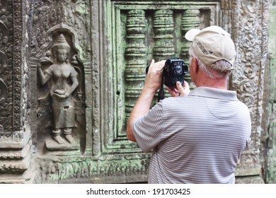 SIEM REAP, CAMBODIA - APR 07: Man takes picture of Apsara dancer in Angkor Wat temple, Angkor archaeological park, Cambodia. On April 07, 2014.
