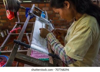 SIEM REAP, CAMBODIA - AUGUST 24, 2015: A girl weaves with silks at a silk farm.