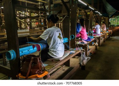 SIEM REAP, CAMBODIA - AUGUST 24, 2015: Women weave decorative cloths with silks at a silk farm.