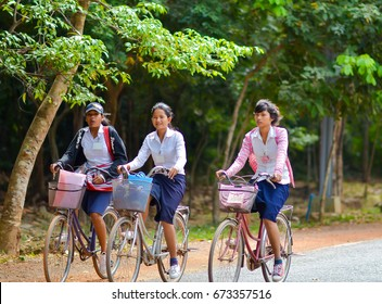 Siem Reap, Cambodia - Circa December 2011 - Portrait of an unidentified Cambodian schoolgirls in school uniform riding bicycles home from school on a quiet road surrounded by green trees