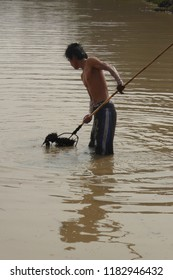 SIEM REAP, CAMBODIA - FEB 15, 2015 - Young man uses a rake to catch  fish in a irrigation pond  near Siem Reap,  Cambodia