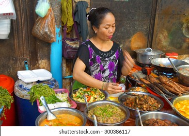 SIEM REAP, CAMBODIA - FEB 16, 2015 - Woman cooking lunch in the market of  Siem Reap,  Cambodia