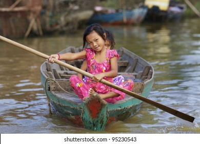 SIEM REAP, CAMBODIA - JAN 23: Two children rowing rowing boat on Tonle Sap Lake in Siem Reap, Cambodia on January 23, 2012. Tonle Sap is the largest freshwater lake in SE Asia peaking at 16k km2.