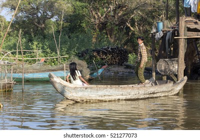 SIEM REAP, CAMBODIA - JANUARY 2, 2014: People in a floating village on the bank of Tonle Sap Lake. Tonle Sap is the largest freshwater lake in SE Asia peaking at 16k km2