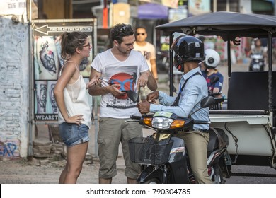 SIEM REAP, CAMBODIA - January 9, 2018: Tourists negotiating with tuk-tuk driver in Siem Reap, Cambodia on January 9, 2018.