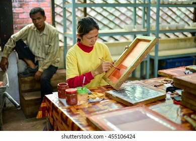 SIEM REAP, CAMBODIA - JULY 15, 2016: Woman artisan focus and concentrate making art paint at local craft center. Selective focus