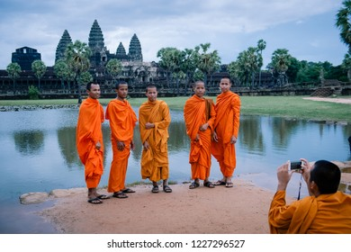 Siem Reap, Cambodia - July 16, 2017: Four novice Buddhist monks being photographed by their friend by a lake, with Angkor Wat in background.