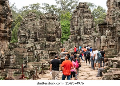 Siem Reap, Cambodia - July 28, 2018: Tourist visiting in Bayon temple at Angkor Wat complex, Chinese tour group sightseeing. Khmer architecture heritage in Siem Reap, Cambodia