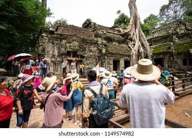 Siem Reap, Cambodia - July 28, 2018: Tourist visiting in Ta Prohm at Angkor Wat complex, Chinese tour group sightseeing. Khmer architecture heritage in Siem Reap, Cambodia