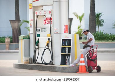 SIEM REAP, CAMBODIA - JUNE 29, 2014: An unidentified worker stands counting money at an empty petrol station. Petrol is not cheap in Cambodia - about 1.46 US dollars for 1 litre of petrol 95.